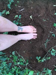Feet with tattoo in dirt and plants