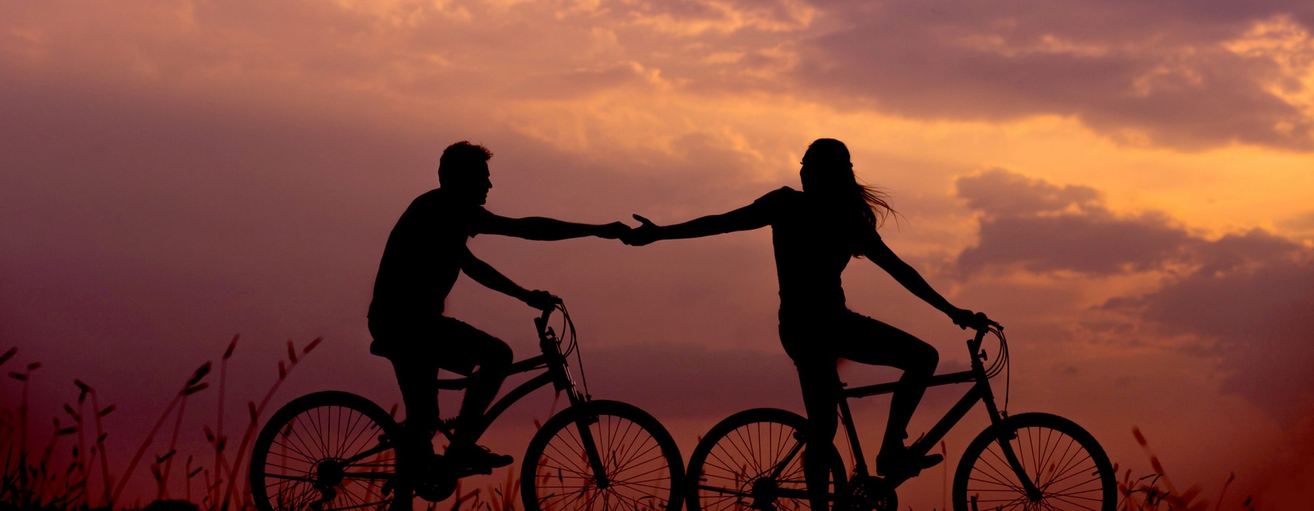 Couple riding bikes at sunset with their hands outstretched