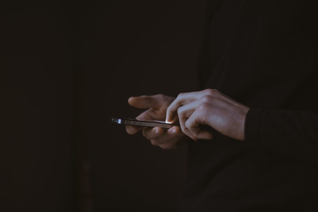 Man using iPhone in a black longsleeve shirt