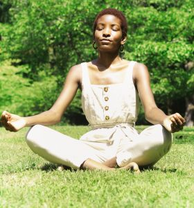 Black woman meditating outside in fashionable overalls